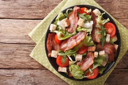 Spicy salad of bacon, tomato, croutons and lettuce close-up on a plate on a table. Horizontal view from above