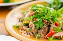 Spicy salad of roasted beef , Thai style food ; selective focus with blur background.