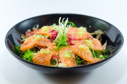 Spicy Salmon Salad with vegetable in black bowl on white background