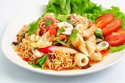 Spicy Seafood Instant Noodle Salad. Instant noodle spicy salad with shrimp, squid, Mussels, crab sticks, fresh vegetables, tomatoes, onions. Thai food style.
