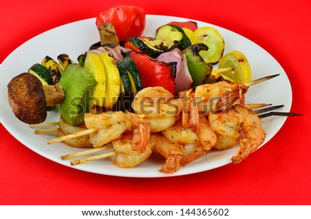 Spicy shrimp and assorted vegetables on wooden skewers cooked to perfection over open grill fire served on white plate against bright red background.