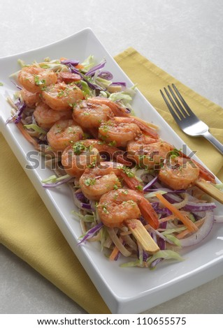 Spicy shrimp skewers on coleslaw salad with yogurt cucumber dill dressing