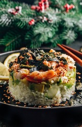 Spicy shrimp sushi stacks with layers of sushi rice, cucumbers and avocado in addition to the spicy shrimp and furikake on dark christmas festive backgraund. Selective focus. Vertical photo