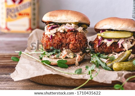 Spicy southern style fried chicken sandwich with coleslaw and pickles. Toasted burger buns. Fast food. Deep fried chicken.Rustic food photo.Crispy chicken breast.Breaded fried chicken. Unhealthy food.