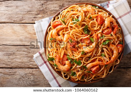 Spicy spaghetti with shrimps in tomato sauce close-up on a plate. horizontal top view from above