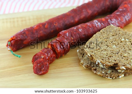 Spicy Spanish Chorizo, Cured Paprika sausage, with wholewheat bread on a wooden cutting board