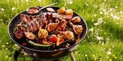 Spicy spare ribs, assorted veggies and chicken drumsticks grilling on a portable barbecue outdoors in a spring meadow with dandelions in a panorama format