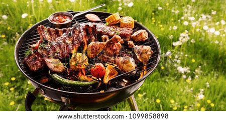 Spicy spare ribs, assorted veggies and chicken drumsticks grilling on a portable barbecue outdoors in a spring meadow with dandelions in a panorama format #1099858898