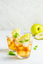 Spicy summer apple cocktail, apple iced tea in glasses. Space for text.