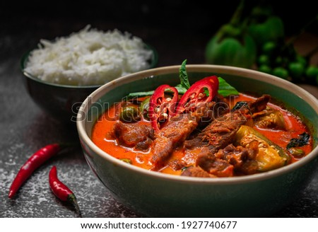 spicy thai curry with pork meat serving with rice and decorating with herbal vegetable ingredients like chili and eggplant on rustic background - Thai food