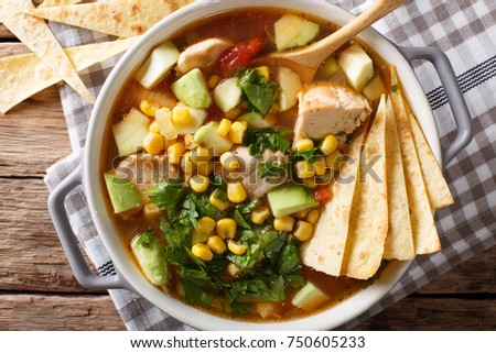 spicy tortilla soup with chicken, cilantro, tomatoes, avocado and corn close-up on the table. horizontal top view from above