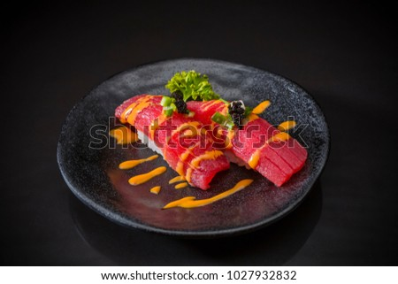 Spicy Tuna Nigiri, Sushi Tuna with Spicy Sauce served on traditional Japanese food on ceramic dish, Japanese food style, Sushi Menu, sushi tuna, maguro sushi on black background, selective focus