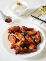 spicy wing on white plate, served with Chili sauce and rice. with white property. napkins and chopstick