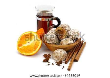 Spicy winter hot drink with orange, spices and spice-cakes on a white background.