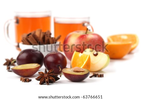 Spicy winter hot drink with oranges, apples, plums, cinnamon, anise and clove isolated on white background