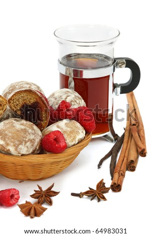 Spicy winter hot drink with raspberry, spices and spice-cakes on a white background.