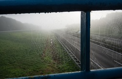 Spider webs with dewdrops in the railing of an overpass over a motorway