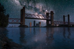 Spijkenisse bridge at night with milky way. River Maas waterfront view of open bridge part and the skyline of Spijkenisse on the background. Photomanipulation