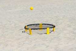 Spike ball game with yellow ball on sand. Summer game concept