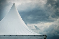 Spiked roof of white party event tent against sky with dark clouds.