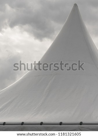 Spiked roof of white party event tent against sky with dark clouds. #1181321605