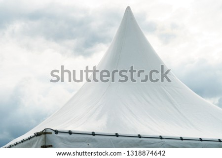 Spiked roof of white party event tent against sky with dark clouds. #1318874642