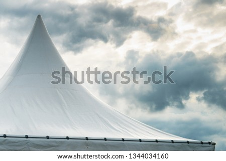 Spiked roof of white party event tent against sky with dark clouds. #1344034160