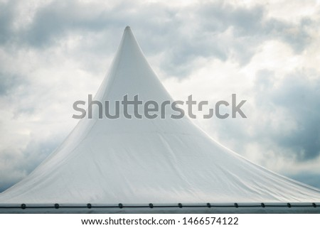 Spiked roof of white party event tent against sky with dark clouds. #1466574122