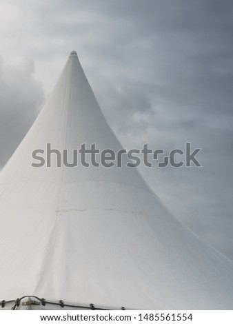 Spiked roof of white party event tent against sky with dark clouds. #1485561554