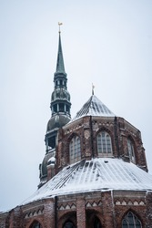 spiky spire of an ancient building with a golden rooster at the top. snow-covered roof of an old building in the old town