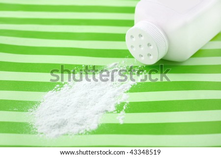 Spilled baby scented powder on striped green background with short depth of field