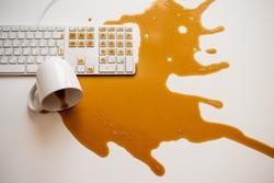 Spilled black coffee on a computer keyboard at a white table