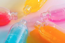 Spilled bottles of colorful shampoo, on white