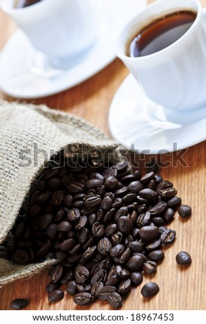 Spilled coffee beans and cups of espresso
