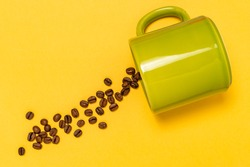 Spilled coffee beans from the green ceramic cup  on the yellow background