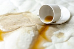 Spilled coffee on the bed. Unlucky, unfortunate breakfast. Accidentally dropped cup with saucer on white bedsheet. Wet spot.