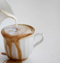 Spilled coffee with milk in a white cup  and white background