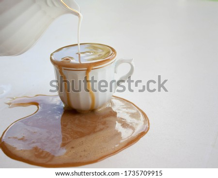 Spilled coffee with milk in a white cup  and white background ストックフォト ©
