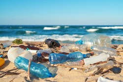 Spilled garbage on the beach of the big city. Empty used dirty plastic bottles. Dirty sea sandy shore the Black Sea. Environmental pollution. Ecological problem. Moving waves in the background