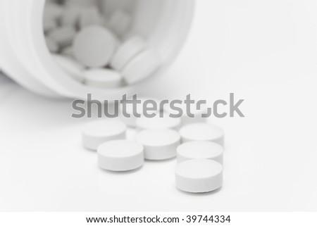 Spilled pills from open prescription medication bottle
