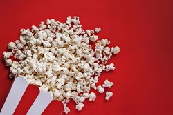 Spilled popcorn on a red background. Snack. Film premiere. Rating of the best movies. Watch a movie. The atmosphere of the cinema. Movie night.