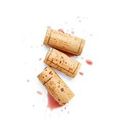 Spilled red wine and corks isolated on white background