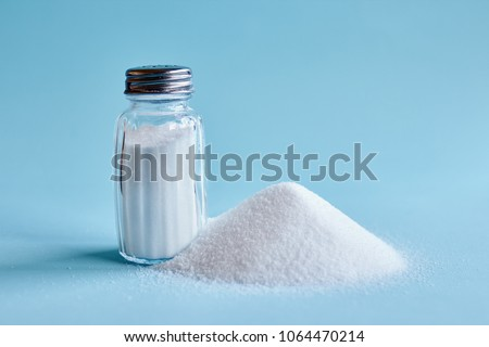 Spilled salt and saltshaker on blue background #1064470214