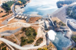 Spillway of Jindabyne lake power hydro dam on Snowy River in Snowy Mountains of Australia - aerial top down view.