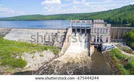 Spillway on old hydroelectric power station in sunny day aerial view #675444244