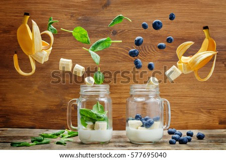 Spinach banana and blueberry banana smoothie with flying slices on a wood background. toning. selective Focus #577695040