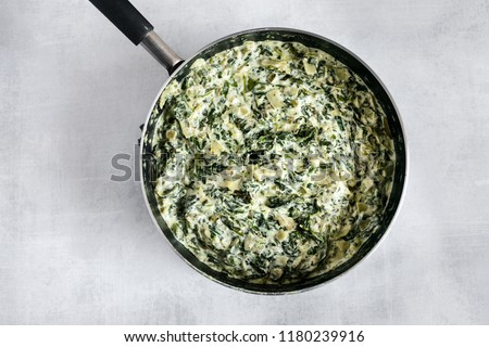 Spinach dip in a black pot ready to be served and eaten. Granite table top somewhat cement like as well. Great sport snack while watching the game or fight.  #1180239916