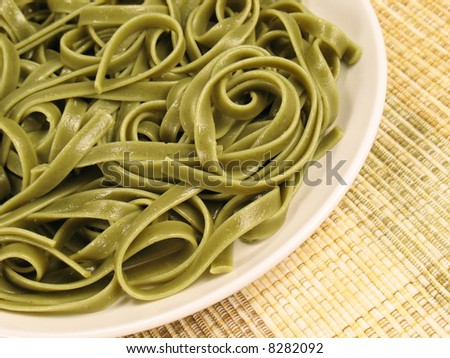 Spinach fettuccine with extra virgin olive oil on a white plate.