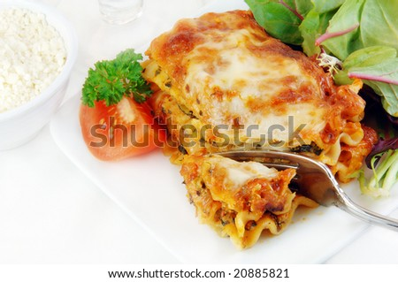 Spinach lasagna with salad on a white plate.
