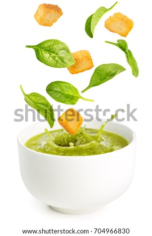 spinach leaves and croutons falling into a soup bowl isolated on white